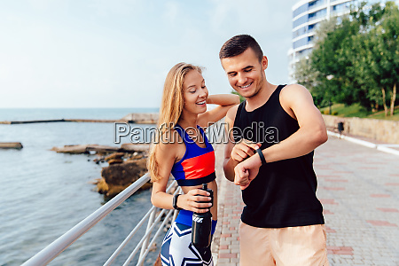 cheerful sportsman and sportswoman checking a