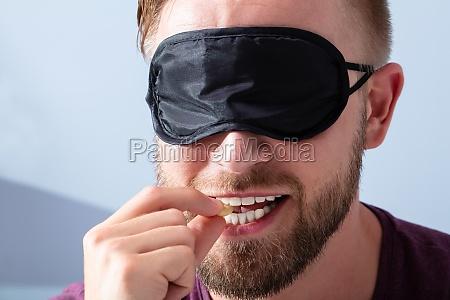 blindfolded man testing food