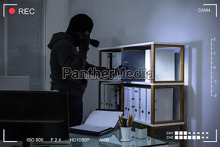 thief stealing file from shelf