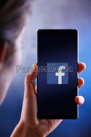 woman holding smartphone displaying logo of
