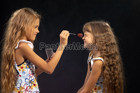 girl powdering nose to her sister