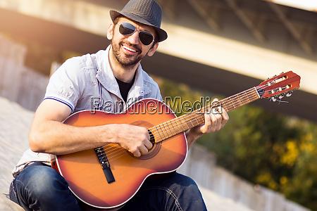 hipster guy playing guitar