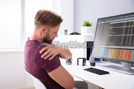 man sitting on chair suffering from