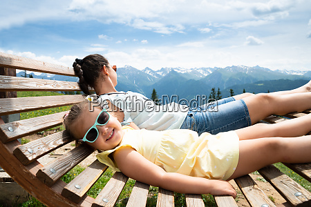 girl and mother relaxing in sun