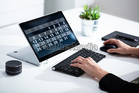businesswoman using calendar on laptop