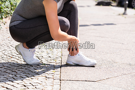 female jogger suffering from ankle injury