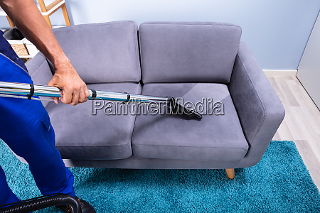 man cleaning sofa with vacuum cleaner