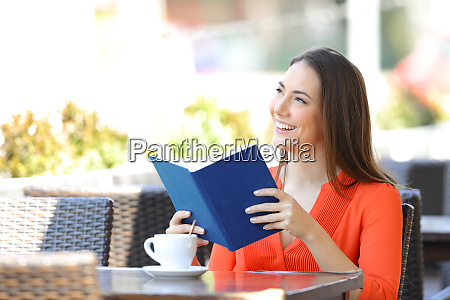 happy woman reading a book dreaming