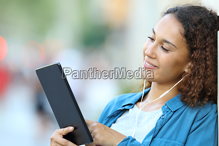 mixed race woman listening music with