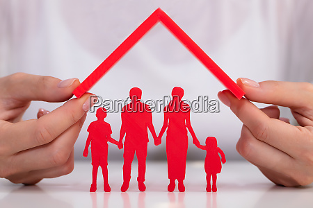 businesswoman protecting family figures with roof