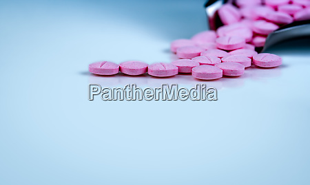 pink tablets pills on blurred background
