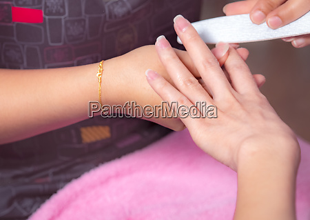 woman receiving fingernail manicure service by