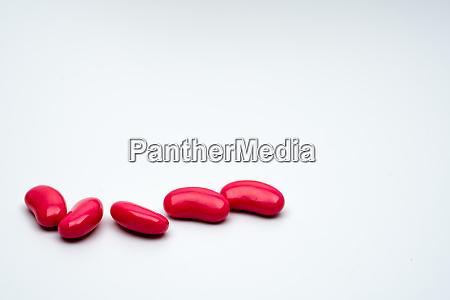 five red kidney shape sugar coated