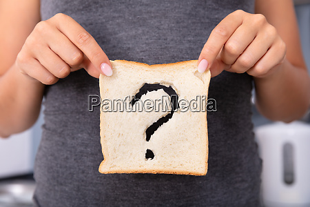 woman holding slice of bread with