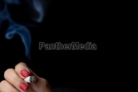 cigarette with smoke in woman hand