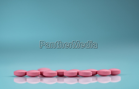pink round tablets pills with shadow