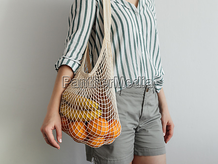 woman standing with mesh bag on