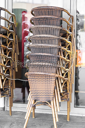 rattan chairs are stacked in front