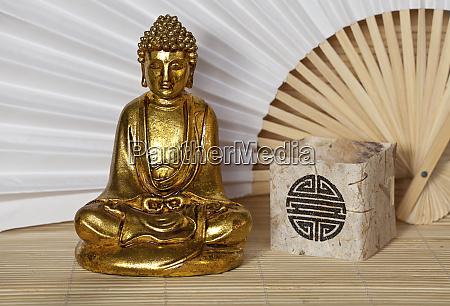 golden buddha statue on bamboo background