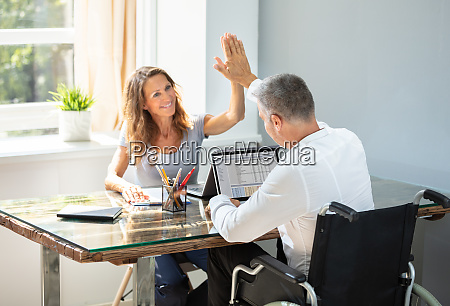 disabled businessman giving high five to