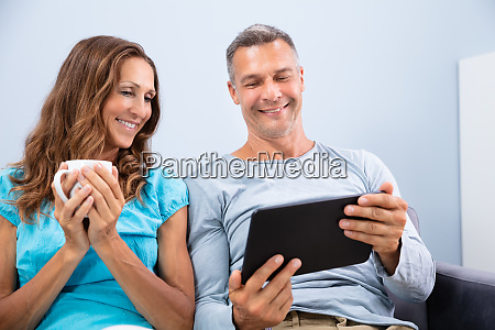 couple sitting on sofa watching video