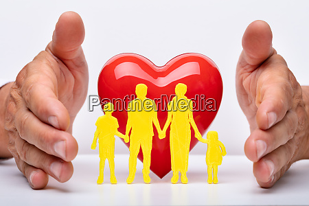 persons hand protecting family cut out