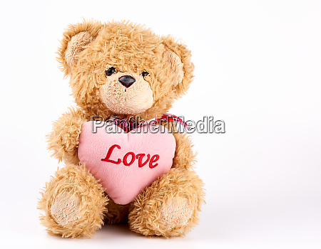 beige teddy bear holds a pink