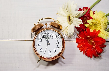 clock flowers and books concept of