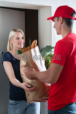 delivery man giving grocery bag to