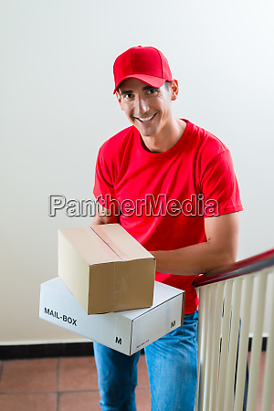 delivery man holding two cardboard boxes