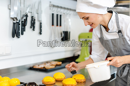 confectioner working on sweet little cakes