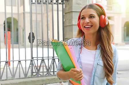 smiling student girl with headphone outdoors