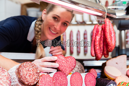sales woman in meat shop showing