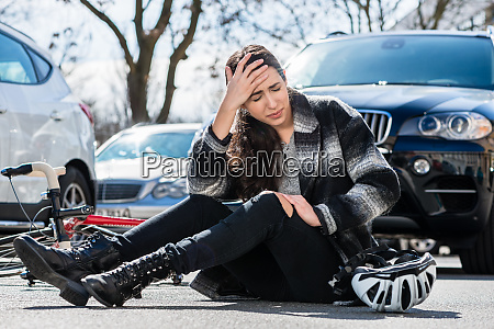 young woman sitting on the asphalt