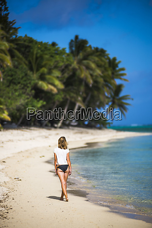 woman walking along a tropical beach