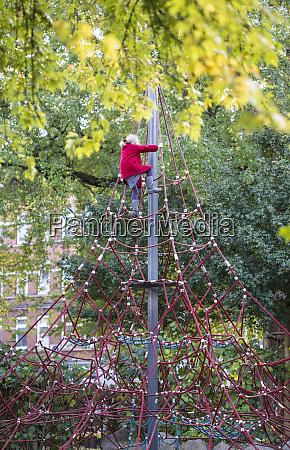 little girl climbing on jungle gym