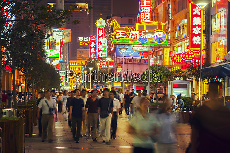 shoppers in neon lit streets shanghai