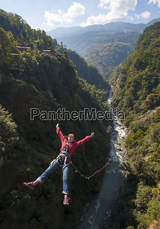 a girl jumps a canyon swing