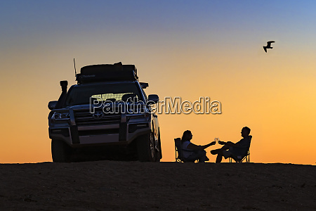 couple toasting a sunset next to