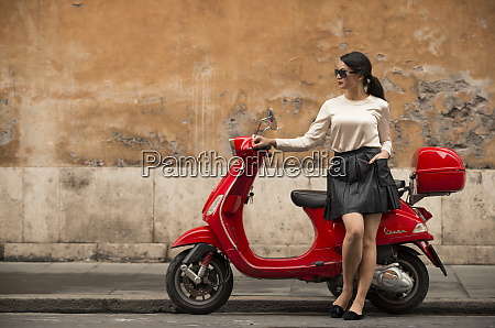 young woman waiting by vespa moped