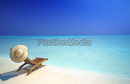 wooden deckchair and hat on tropical