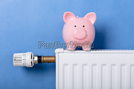 piggy bank on heating radiator with