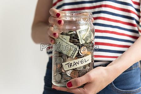 woman holding travel savings jar