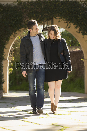 young couple walking by arch