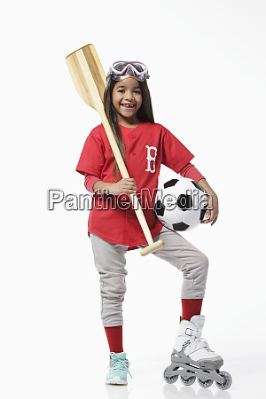 girl dressed in baseball uniform holding