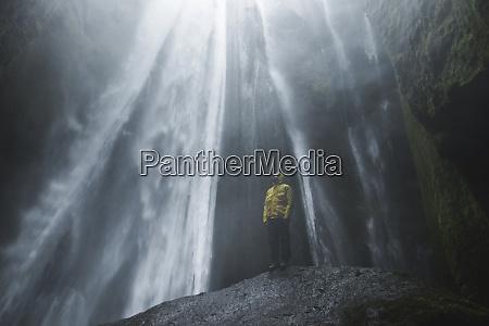 man wearing yellow raincoat by seljalandsfoss
