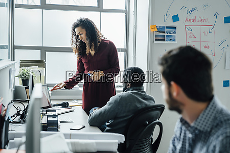 coworkers using laptop in office