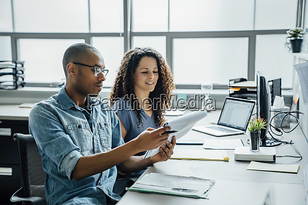 coworkers with note pad in office