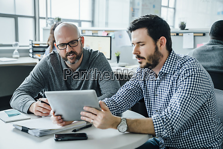 men using digital tablet during meeting