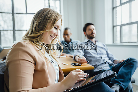 woman using digital tablet during meeting